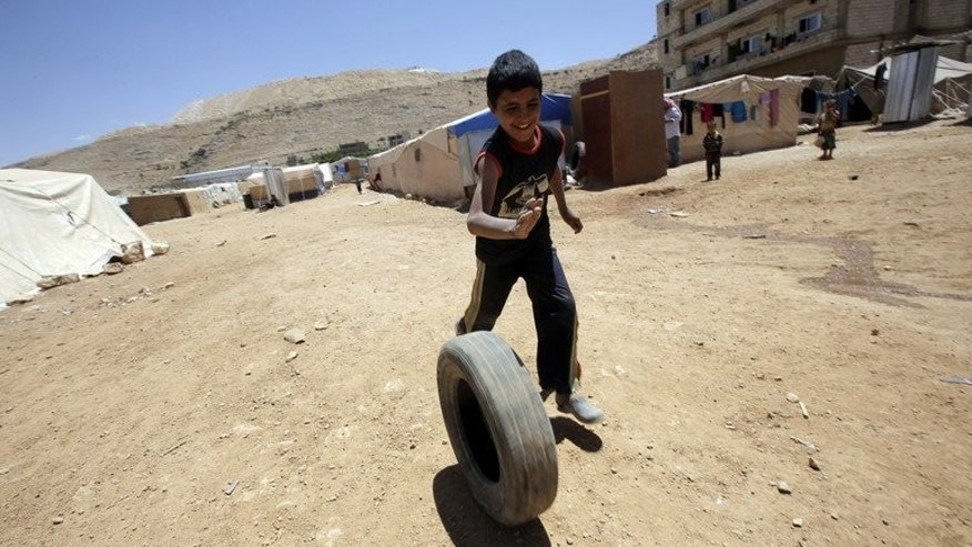 A young Syrian boy, who fled with his family after recent violence in Qusayr, plays with a tyre at the Arsal refugee camp on June 14, 2013 in Lebanon. A majority of Lebanese believe the influx of Syrian refugees in their country threatens national security, Norway's Fafo research foundation said in a report obtained on Thursday by AFP.