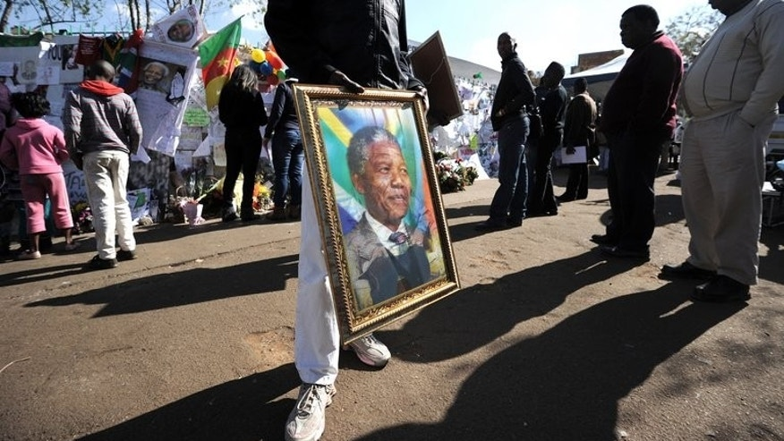 "A man sells a portrait of former Nelson Mandela on Thursday outside the MediClinic Heart Hospital in Pretoria. Mandela ""continues to respond to treatment"" but is still in a critical condition in hospital, South Africa's presidency said Thursday."