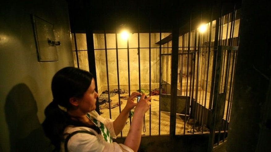 "An Iraqi Kurd visitor takes pictures of cells at a former torture centre on May 28, 2013. Officially called the ""National Museum In Order Not To Forget"", locals still refer to it by its Saddam-era nickname."