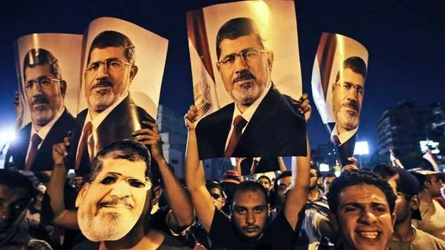 July 10, 2013:  Supporters of ousted Egypt's President Mohammed Morsi, hold posters of him as they protest during the Islamic month of Ramadan, in Nasr City, Cairo, Egypt.