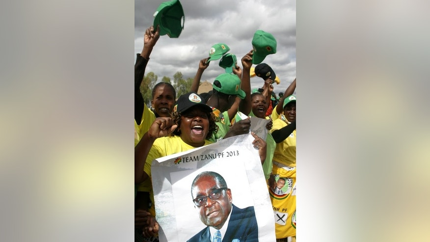 Supporters of the president of Zimbabwe hold a poster with his picture as they attend an election campaign rally in Mashonaland Central province July 11, 2013.