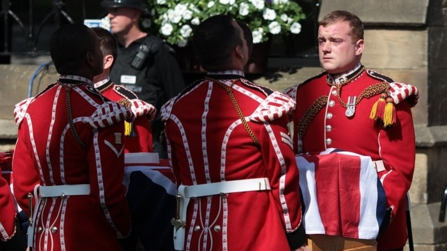 Royal Fusliers carry the coffin of Lee Rigby into Bury Parish Church for a vigil on the eve of his funeral on July 11, 2013. Friends and family of a British soldier murdered on a London street in a suspected Islamist attack will pay their respects at his funeral in northern England on Friday.