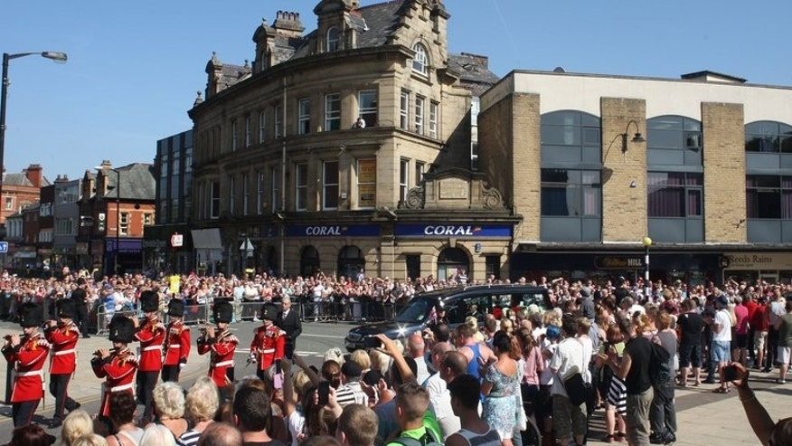 Crowds watch as the hearse carrying the coffin of Fusilier Lee Rigby arrives at Bury Parish Church for a vigil on the eve of his funeral on July 11, 2013.