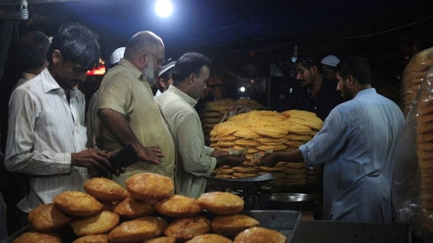Pakistani Muslims buy traditional food for Ramadan at a shop in Karachi on July 10, 2013.