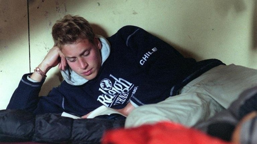 Britain's Prince William relaxes with a book at the team's accommodation in the village of Tortel, Chile during his Raleigh International gap year trip to the country on December 2000. Prince William's future has always been mapped out but as fatherhood nears, the 31-year-old shows little sign of giving up the semblance of a normal life he has carved out for himself under the media spotlight.