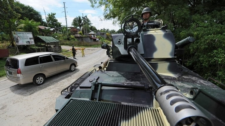 A Philippine soldier (R) aboard an armored personnel carrier (APC) watches vehicles pass a military checkpoint in the town of Datu Piang in the southern Philippine province of Maguindanao on Mindanao island on September 5, 2011. Armed Muslim clans in the strife-torn southern Philippines are holding 11 people, including several children captive, as part of a decades-long feud, the military said.