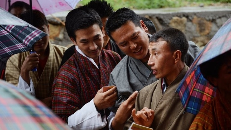 Bhutanese men discuss their voting cards as they wait in line outside a polling station in Paro, on May 31, 2013. Bhutan concludes its second-ever election on Saturday, with the race to form a government too close to call as voters give their verdict on five years of democracy.