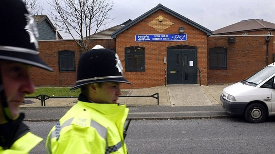 Two British police officers pass Tipton Muslim Community Center on March 11, 2004. British counter-terror police were on Friday investigating reports of an explosion outside a mosque in central England that witnesses said left nails scattered over the ground.