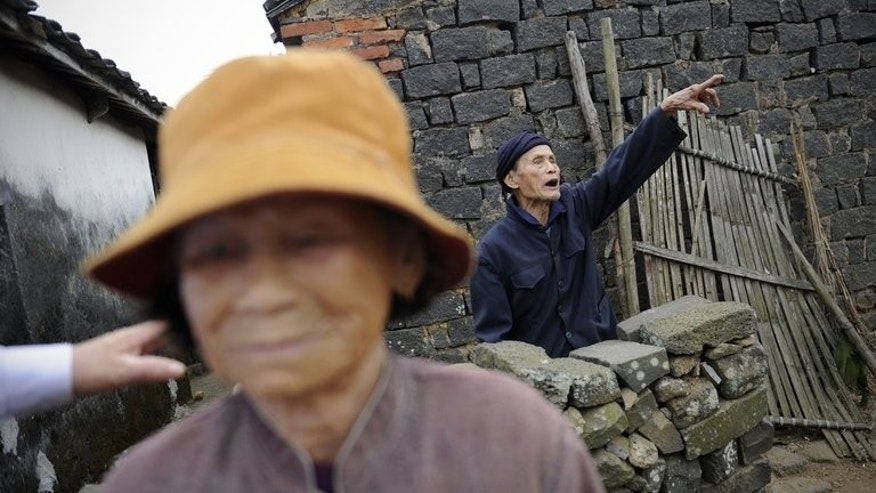 An elderly man, Wang Kaiguo (R), gestures in Chengmai city, in China's southern Hainan province, on January 22, 2013. As China was swept by dramatic changes -- from Japanese invasion, to the Communist victory in the civil war -- most Chengmai residents carried on doing what they had always done, growing crops.