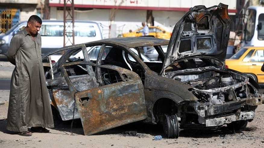 An Iraqi man inspects a burnt-out vehicle after a car bomb explosion in the Hurriyah area of Baghdad, on July 3, 2013. The toll from a wave of attacks in Iraq mainly targeting security forces and Shiites has risen to 51 killed, 26 of them police and soldiers, security officials and doctors said.