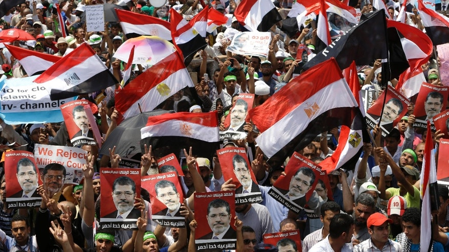 "July 12, 2013 - Supporters of Egypt'ss ousted President Mohammed Morsi, wave Egyptian flags and hold portraits of Morsi with Arabic words that read: ""Mohammed Morsi, legitimacy red line"" during demonstration at Nasr city, Cairo, Egypt. Thousands of Muslim Brotherhood supporters rallied in a Cairo city square, chanting anti-military slogans, deriding army chief who led Morsis removal as traitor with one ultraconservative Salafi cleric vows to stay in the streets for years until Morsi is reinstated."