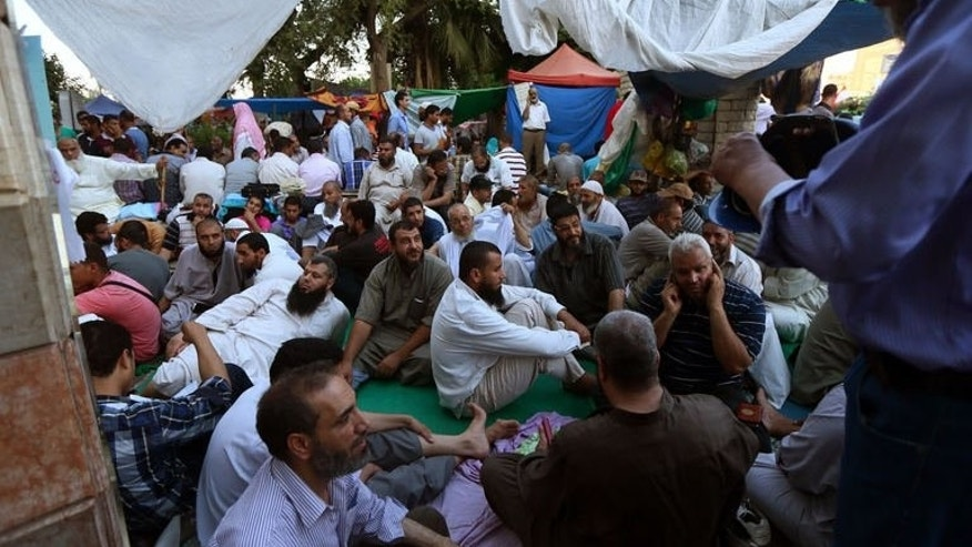 Supporters of ousted Egyptian president Mohamed Morsi, wait to break their fast outside Cairo's Rabaa al-Adawiya mosque on July 12, 2013.