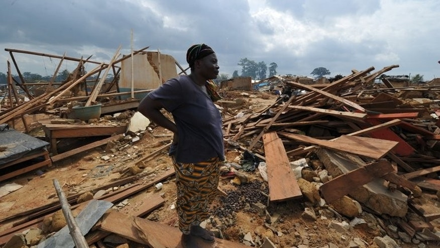 A woman looks at the ruins of Baleko-Niegre village that was completely razed during a military operation to save the protected Niegre forest, on June 22, 2013. The Ivorian government sent troops and buldozers to reclaim the forest in southwestern Ivory Coast, leaving thousands of farmers, who had been illegally exploiting the land for years, without work and without homes.