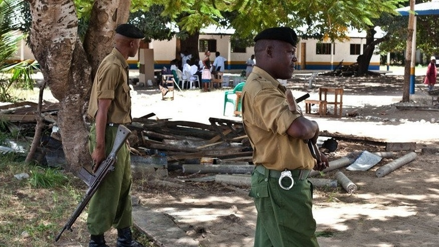 File picture shows police officers on guard at a polling station in Kakuyuni in the coastal Kenyan town of Malindi on February 24, 2013. Three foreigners facing terrorism charges at home have been charged with illegally entering Kenya and are set to be deported, lawyers and officials said Friday.