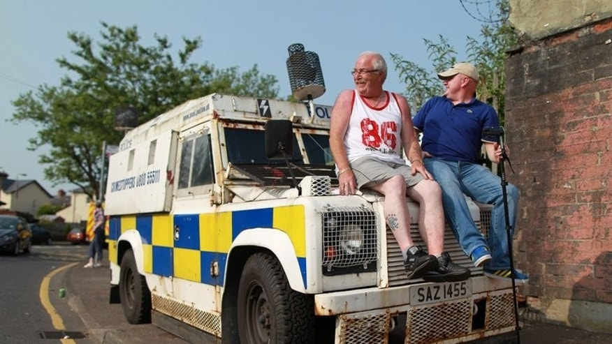 Two spectators sit on the bonnet of an armoured police vehicle as protestant Orangemen march through the Catholic Ardoyne district of north Belfast, Northern Ireland, on July 12, 2013. A leading Northern Irish politician was knocked unconscious by a thrown missile as sectarian tensions spilled over into rioting in Belfast at the climax of the Protestant marching season.