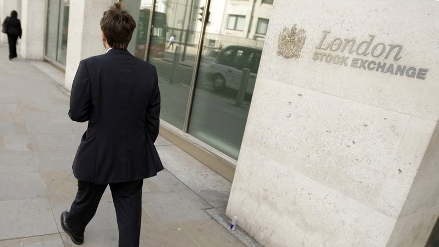City workers walk past the London Stock Exchange. London shares closed flat on Friday as higher inflation data in the US dampened confidence slightly after Thursday's strong rise, dealers said.
