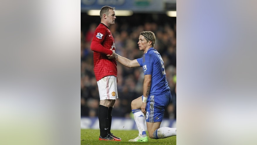 Wayne Rooney helps Chelsea's Fernando Torres to his feet in a Premier League game at Stamford Bridge last October. Jose Mourinho is seeking a striker to complement the erratic Torres and he has brought back Romelu Lukaku after a loan spell at West Bromwich Albion following his return to the London club.
