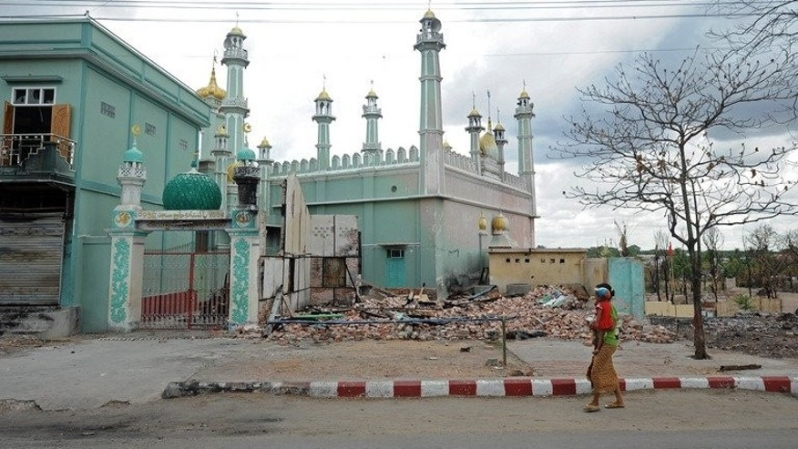 A woman carrying a child walks past a damaged mosque in riot-hit Meiktila, central Myanmar, June 4, 2013. Myanmar has sentenced more than 20 Buddhists to prison for their roles in religious riots in March, including a deadly attack on a Muslim boarding school, lawyers and police said Friday.