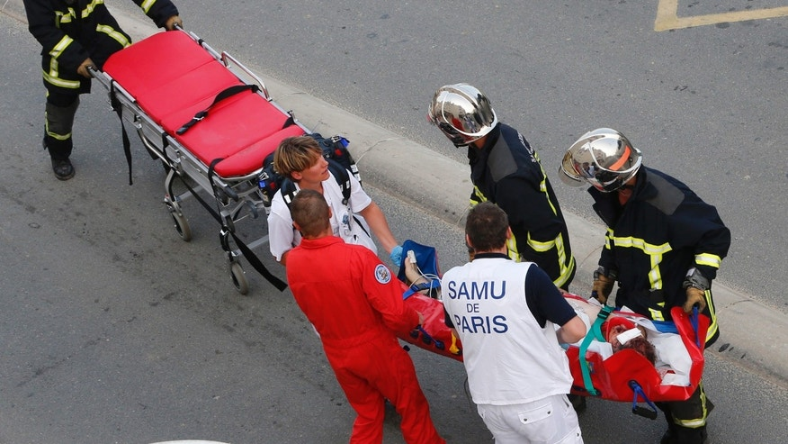 July, 12, 2013 - Rescue workers transport a victim from a train that derailed in Bretigny sur Orge, south of Paris.
