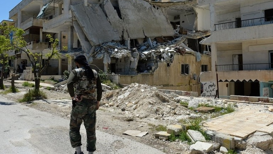 A Syrian rebel walks past a destroyed building in Salma in the coastal province of Latakia on April 26, 2013. An Al-Qaeda front group operating in Syria has killed a rebel chief in a firefight in the province, a monitoring group said.