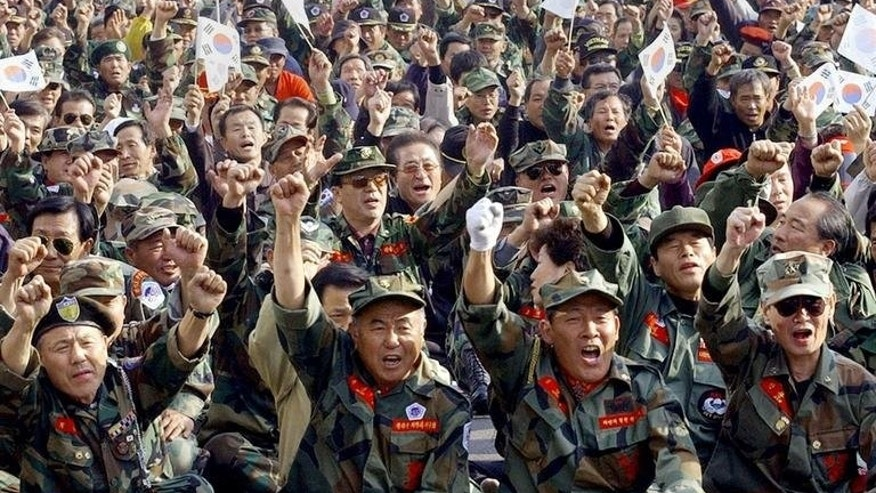 South Korean Vietnam War veterans shout slogans during a rally near the National Assembly in Seoul, October 29, 2004. South Korea's highest court on Friday upheld a ruling ordering two US Agent Orange makers to compensate 39 Vietnam War veterans, while sending another decision back to a lower court for review.