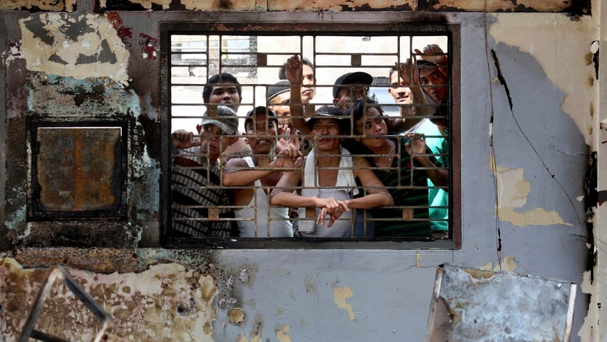 July 12, 2013 - Inmates look out from inside a burned office at Tanjung Gusta prison following a prison riot in Medan, North Sumatra, Indonesia. Security forces regained control of the crowded prison where inmates set fires and started a deadly riot that left five people dead and hundreds of prisoners, including convicted terrorists, on the loose, officials said.