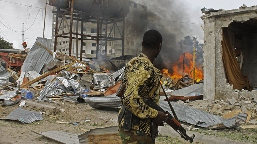 A Somali National Government (SNG) soldier walks past burning debris after a suspected suicide bomber rammed a car laden with explosives into an armoured convoy of African Union troops in Mogadishu on July 12, 2013.