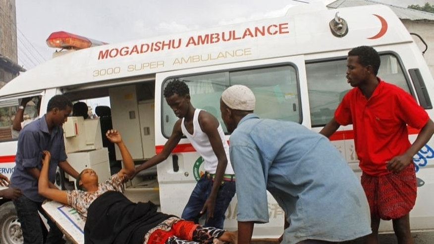 A victim of a suspected suicide bomber who rammed a car laden with explosives into an armoured convoy of African Union troops is carried to an ambulance in Mogadishu on July 12, 2013.