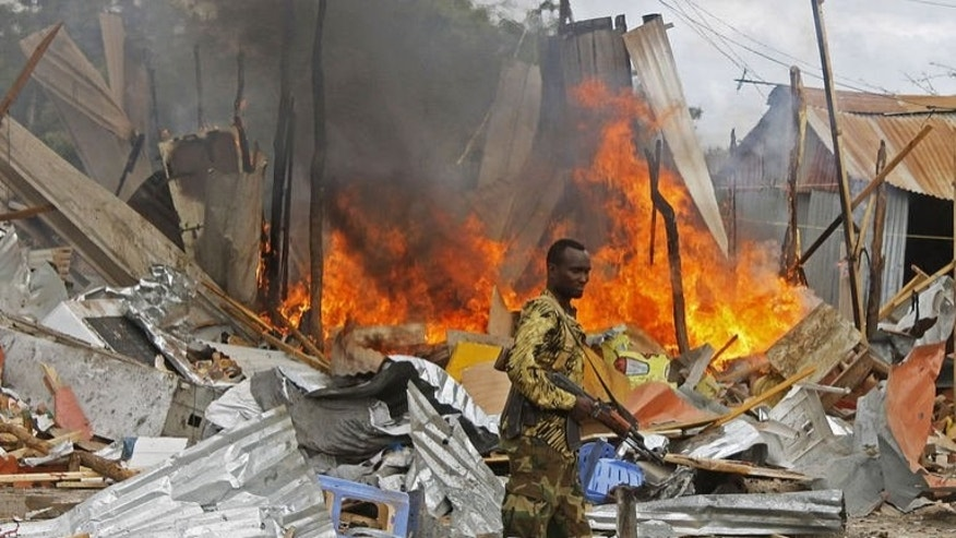 A Somali National Government soldier walks past burning debris after a suspected suicide bomber rammed a car laden with explosives into an armoured convoy of African Union troops in Mogadishu on July 12, 2013.