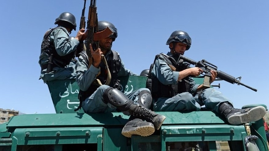 Afghan policemen leave the site of a blast in Kabul on June 18, 2013. A suicide bomber targeted an Afghan police checkpost on the outskirts of Kabul, killing one person and wounding two others on the first Friday of the fasting month of Ramadan, police said.