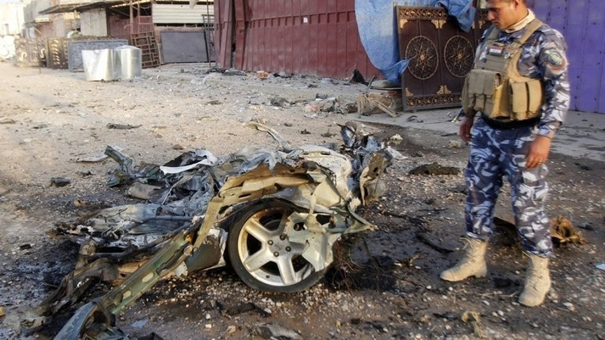 An Iraqi soldier inspects the wreck of a car bomb in the northern Iraqi city of Kirkuk on July 11, 2013. A suicide bomber targeting a cafe in the town killed at least 18 people and wounded 28, police and medical sources said.
