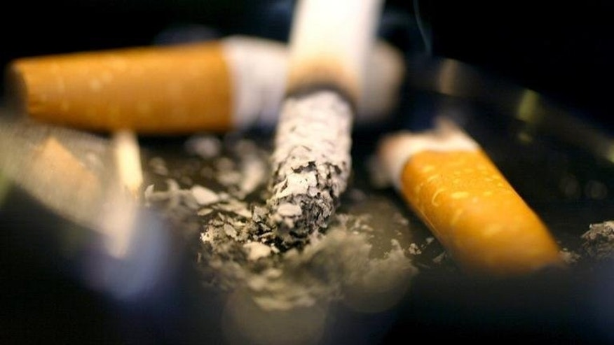 File photo shows cigarettes burning in an ashtray, May 30, 2002. The government on Friday announced that a decision to introduce plain packaging for cigarettes in the UK has been postponed, sparking an angry response from health campaigners.