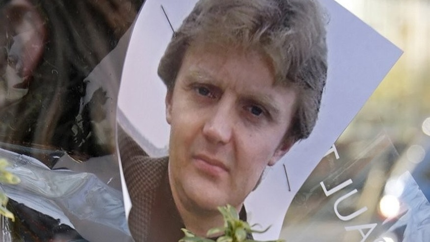 A picture of Russian dissident and former spy Alexander Litvinenko pinned to flowers outside the University College Hospital in central London, November 23, 2007. Britain will not hold a public inquiry into the death of Litvinenko, a coroner said on Friday, leaving the current, lower-level inquest proceedings close to collapse.