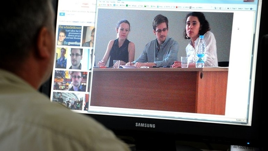 A computer screen displays a picture released by Human Rights Watch of US intelligence leaker Edward Snowden (C) during a meeting with leading Russian rights activists and lawyers at Moscow's Sheremetyevo airport on July 12, 2013. Snowden said he wanted to claim asylum in Russia until he can travel on to Latin America, as Washington kept up the pressure with a warning to Moscow.