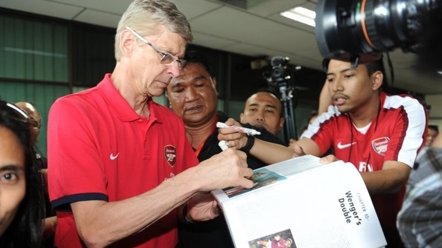 Arsene Wenger signs autographs on arrival in Jakarta's Halim Perdanakusuma airport on Friday. The Gunners boss declined to say if Arsenal were willing to stump up what is thought to be ??40 mn ($60.7 mn) bottom line for Luis Suarez but hinted that a deal may not be entirely dead.