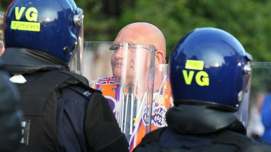 A Orangemen confronts riot police on Shankill road in north Belfast, on July 13, 2013. Police in Belfast were attacked with petrol bombs in a second night of violence by Protestant rioters in the Northern Irish capital.