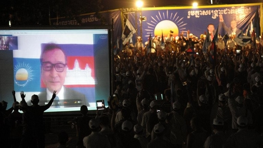 Supporters of the Cambodia National Rescue Party (CNRP) watch Sam Rainsy, President of CNRP, through a video link, during a general election campaign in Kandal province, on July 12, 2013. Exiled Rainsy won a royal pardon on July 12, vowing to return to help his party fight strongman premier Hun Sen who is seeking to extend his nearly three decade grip on power.
