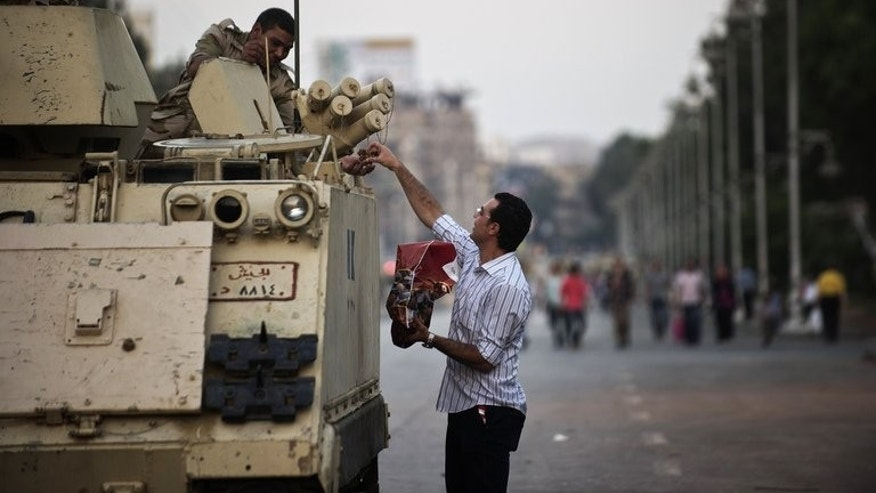 An Egyptian offers dates to soldiers stationed outside the presidential palace in Cairo on July 12, 2013. Egypt's new prime minister planned further talks Sunday on forming a cabinet, as prosecutors looked at criminal complaints against ousted Islamist president Mohamed Morsi and members of his Muslim Brotherhood.