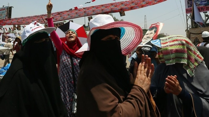 Supporters of Egypt's deposed president Mohamed Morsi chant slogans during a rally outside Cairo's Rabaa al-Adawiya mosque on July 13, 2013. Egypt's new prime minister planned further talks Sunday on forming a cabinet, as prosecutors looked at criminal complaints against Morsi and members of his Muslim Brotherhood