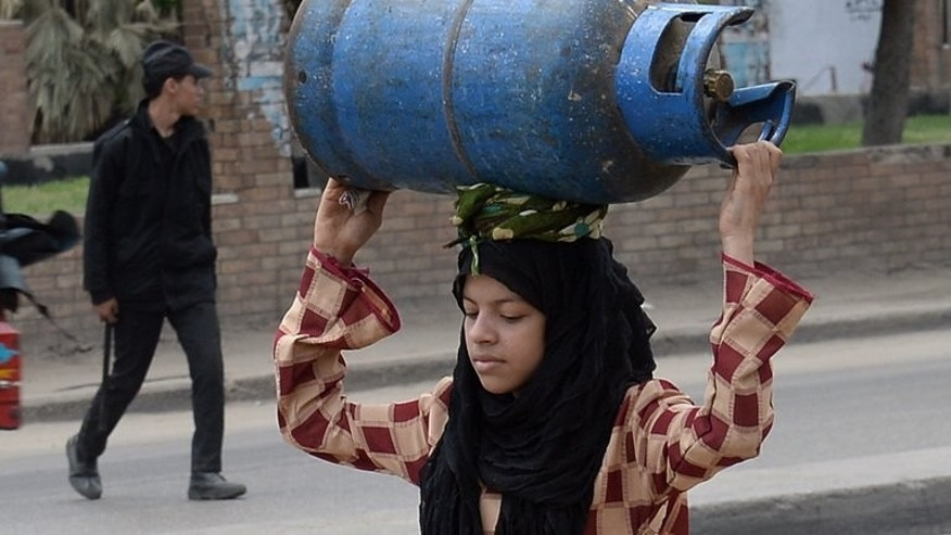 An Egyptian woman carries an empty gas cylinder to be refilled at a warehouse in Cairo on April 4, 2013. Egypt's shattered economy was boosted this week by Gulf allies pledging billions of dollars in aid, but analysts say this simply buys time as political turmoil deepens its economic malaise.