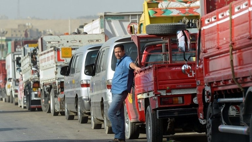 Egyptian motorists line up to buy fuel at a gas station in Cairo on March 11, 2013. Egypt's shattered economy was boosted this week by Gulf allies pledging billions of dollars in aid, but analysts say this simply buys time as political turmoil deepens its economic malaise.