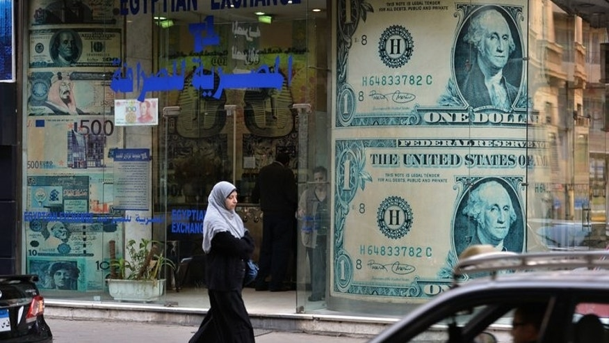 An Egyptian woman walks past a currency exchange store in Cairo on January 6, 2013. Egypt's shattered economy was boosted this week by Gulf allies pledging billions of dollars in aid, but analysts say this simply buys time as political turmoil deepens its economic malaise.
