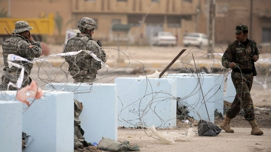 An Iraqi policeman (R) clears the way for US soldiers, near the border with Iran, on January 30, 2009. Clashes between Iraqi border police and gunmen who crossed from Syria into western Iraq killed a policeman and wounded five on Saturday, an officer said.