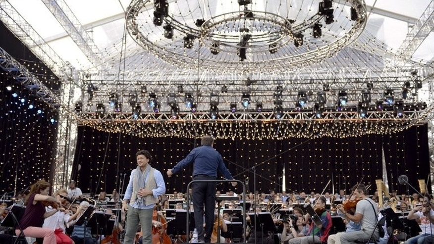 Italian tenor Vittorio Grigolo (L) performs on stage on July 13, 2013 on the Champs de Mars in Paris, during a rehearsal of the Bastille Day concert which will be played by the French National Orchestra and world famous soloists.