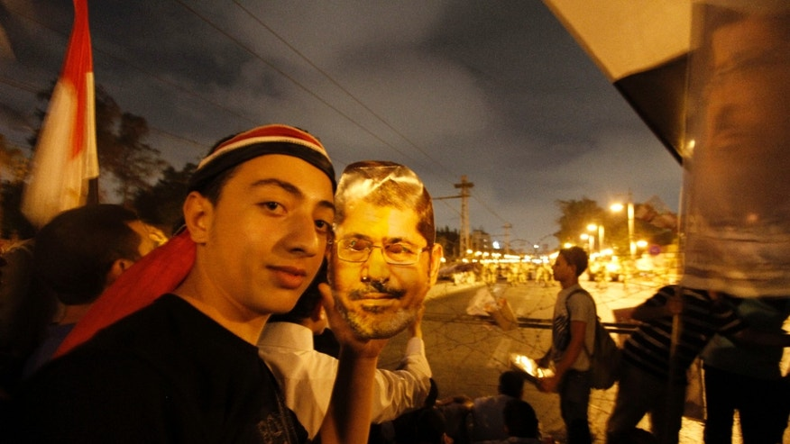 A supporter of Egypt's ousted President Mohammed Morsi poses with a paper mask of Morsi as he and others face the Egyptian military soldiers near the presidential palace in Cairo, Egypt, Saturday, July 13, 2013. Tens of thousands of Islamists rallied Friday in cities across Egypt, vowing to sustain for months their campaign to restore deposed President Mohammed Morsi to power. (AP Photo/Nasser Shiyoukhi)