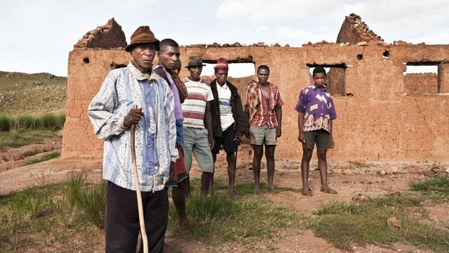 Residents of Asely village, Madagascar, are pictured on February 22, 2013, standing near the debris of a school, reportedly burnt by soldiers. Amnesty International says entire villages were burned and accuses the security services of torture and mass murder during a campaign to end cattle rustling.