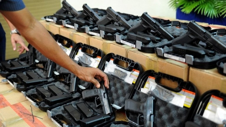 A Philippine police officer inspects pistols during a ceremony in Manila, on July 2, 2013. The Philippines is to investigate a group of police officers who were allegedly filmed executing a criminal, the government's human rights commission said Saturday.