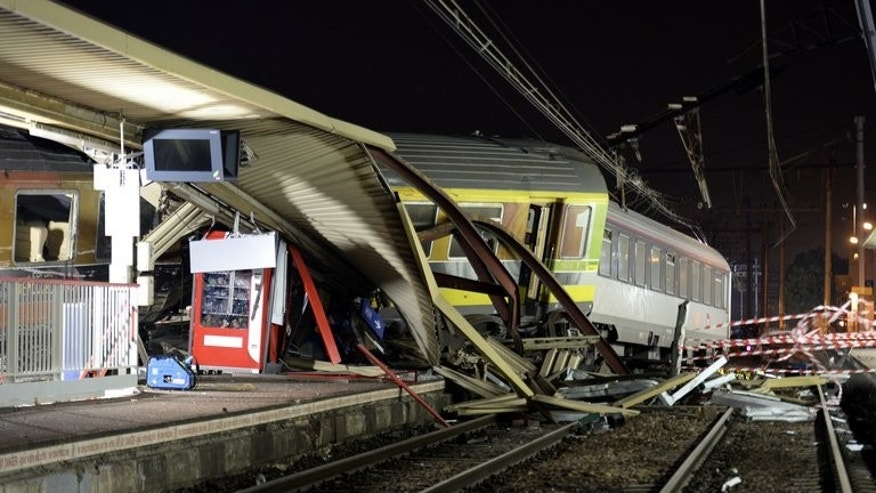 The mangled platform roof and derailed train cars at the site of an accident on July 12, 2013 at Bretigny-sur-Orge, near Paris. Rescue workers searched for survivors early Saturday, hours after a high-speed train derailed killing at least six people and injuring 30 more