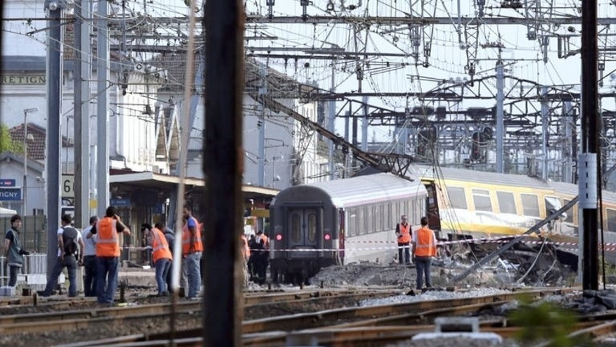 Rescuers work on the site of a train accident in the railway station of Bretigny-sur-Orge on July 12, 2013 near Paris, after a high-speed train derailed killing at least six people and injuring 30 more..
