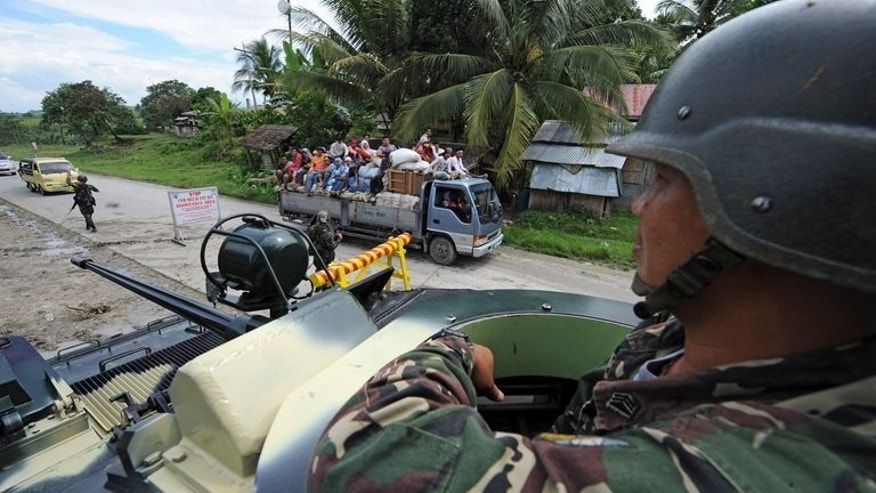 A government soldier aboard an armored personnel carrier is seen at a military check-point on Mindanao island, on September 5, 2011. Fresh fighting between Philippine troops and a renegade group of Muslim rebels left seven people dead on Saturday amid peace talks aimed at ending a decades-old rebellion.